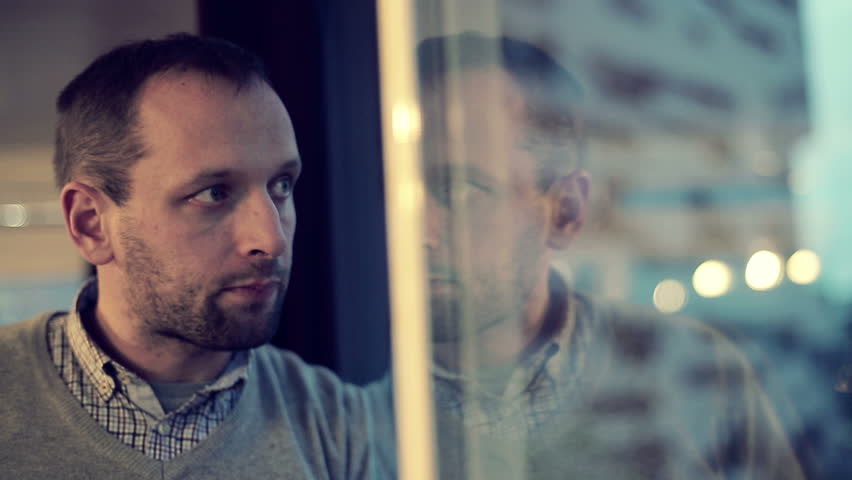 Sad, depressed man drinking tea by the window in home