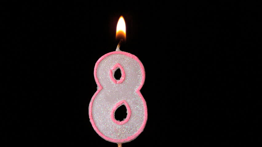 Eight birthday candle flickering and extinguishing on black background in slow motion
