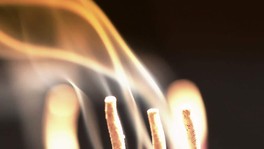 Close up of burning incense sticks with smoke over black background
