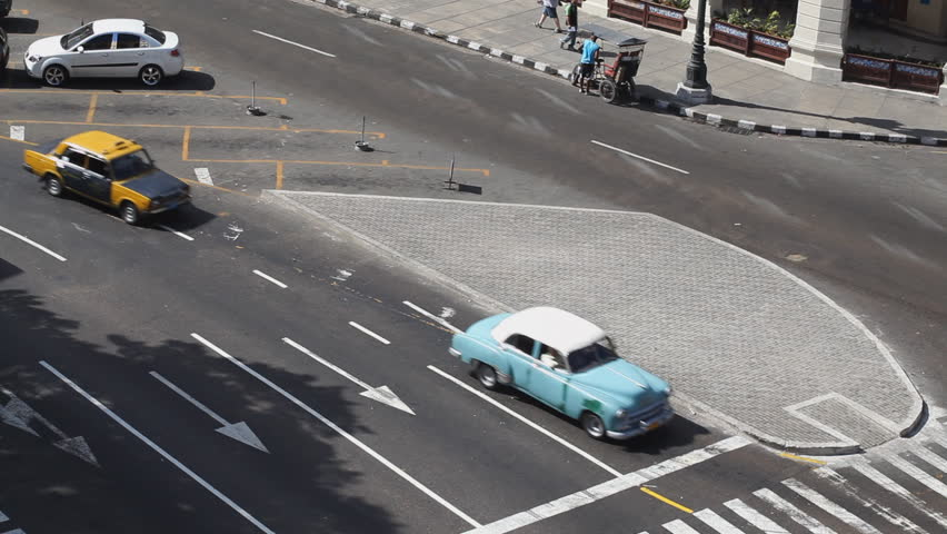 Old Nineteen Fifties American Cars Driving On The Streets Of Downtown Havana Cuba