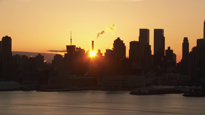 The sun rises behind the buildings of the Manhattan skyline of New York City in a timelapse sequence as viewed over the Hudson River looking east from New Jersey.
