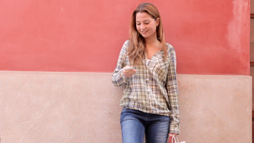 Attractive hispanic young woman using a smartphone while leaning on a colorful wall in the city, smiling and holding shopping bags.