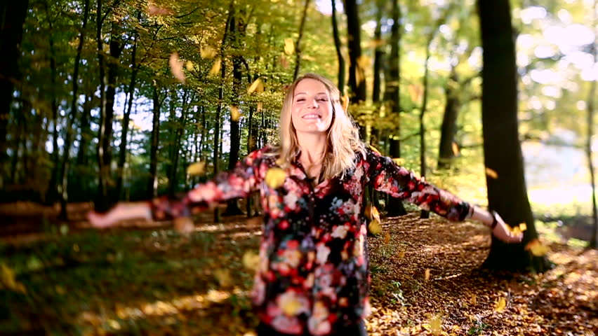 Girl throwing leaves in Autumn in slow motion, smiling into the camera #3576998