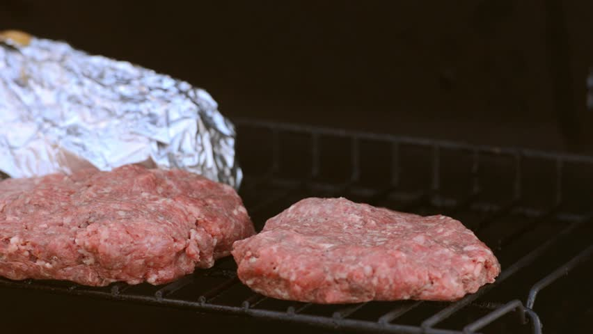 Bratwurst and Burgers being Placed on a Grill