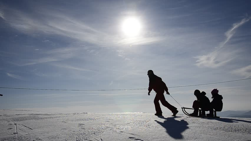 Sporty family silhouette taking a sledge ride over the snow edge with bright sun shining at the back