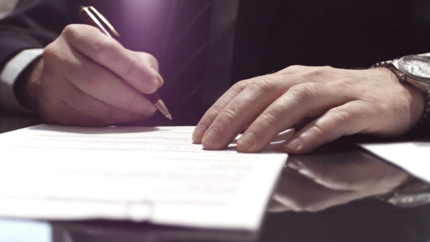 Businessman sitting at shiny office desk signing a contract with noble pen | Shutterstock HD Video #3582926