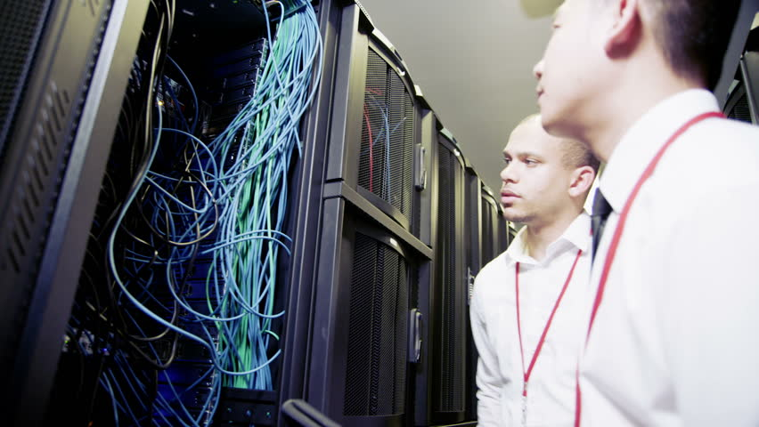 Group of  IT engineers of mixed ethnicity carry out an inspection and maintenance procedure on servers and computers in a data center.