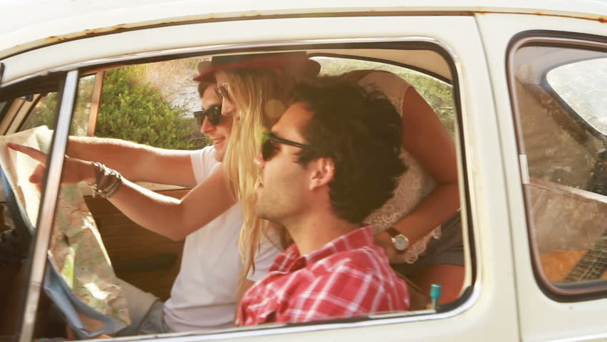 Young Hipster friends on a roadtrip looking at a map.   Shutterstock HD Video #3591254