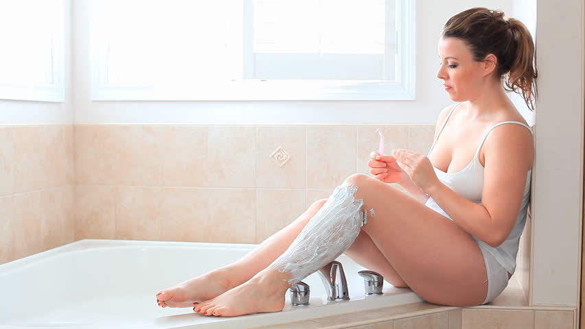 Pretty Young Woman Shaving Her Legs With Shaving Foam And A Razor At Home In Her Bathroom