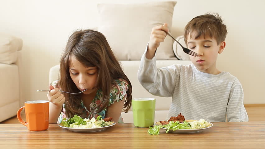 Two adorable kids are having their healthy meal at home.