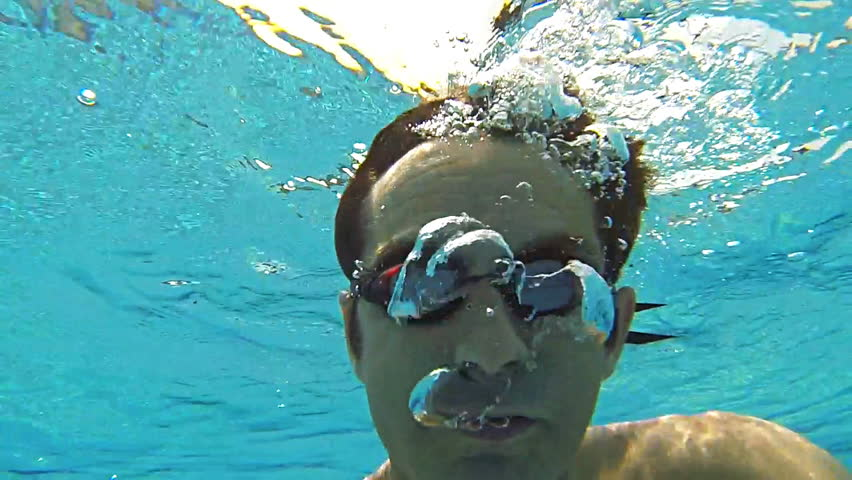 Slow motion underwater scene of a swimmer wearing goggles and breathing out in water