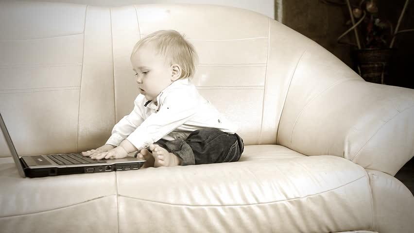 Child sitting on sofa and using laptop