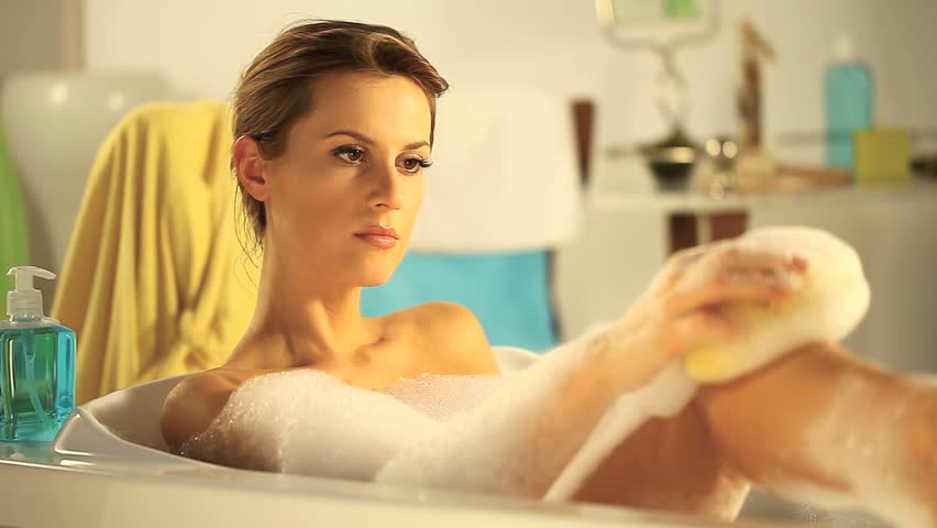 woman taking a bath in a tub full of foam