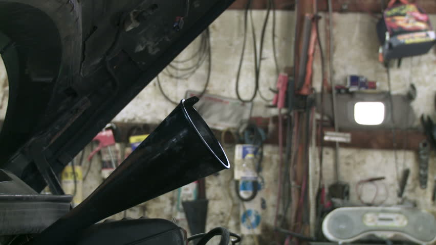 Auto mechanic tops up the oil in a car engine. Detail shot.