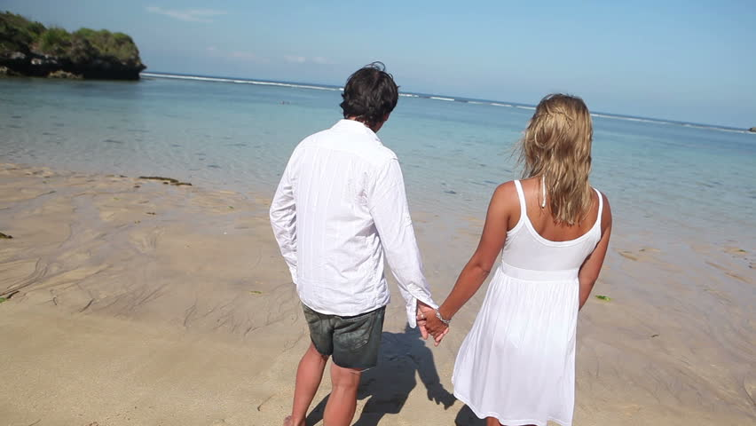 Cheerful couple holding by hands and running together on coastline | Shutterstock HD Video #3671066