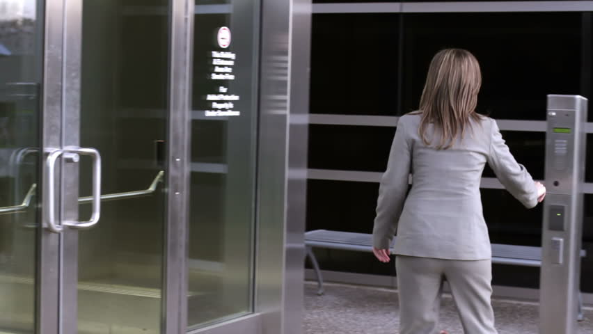 Businesswoman tries repeatedly to use her security pass to enter a modern office