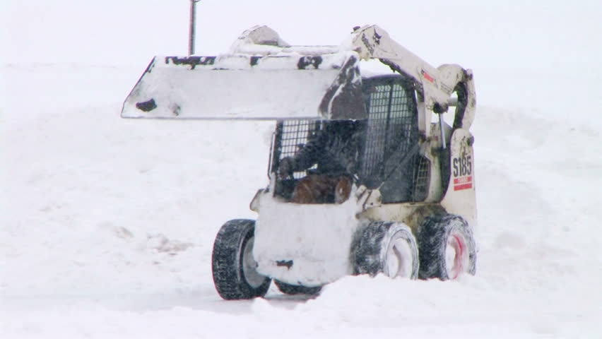Man plowing snow in parking lot.