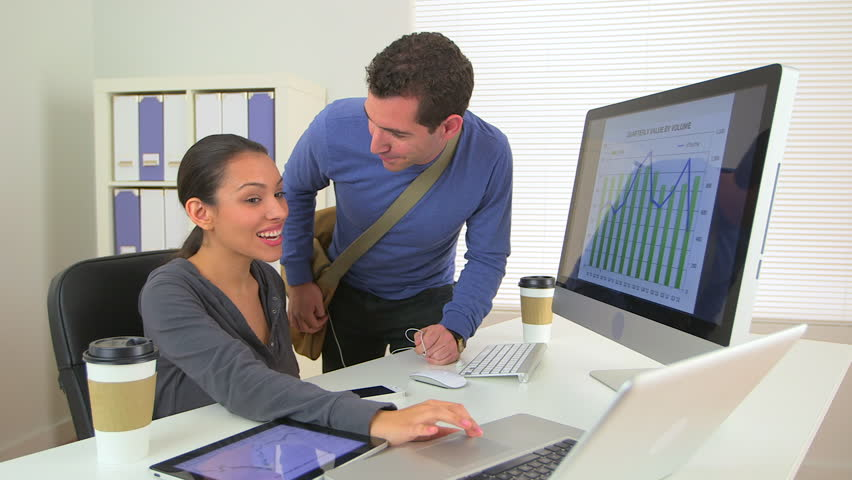 Happy Mexican business woman sharing good news with colleague
