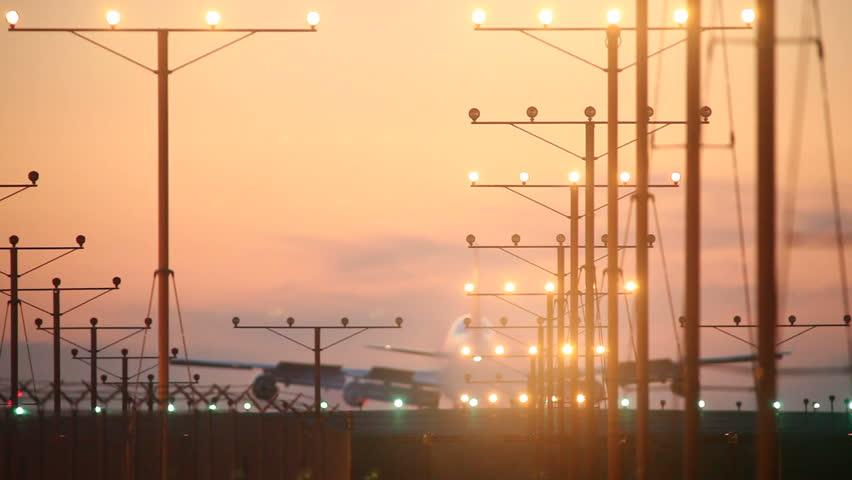 Big airplane landing in airport at sunset