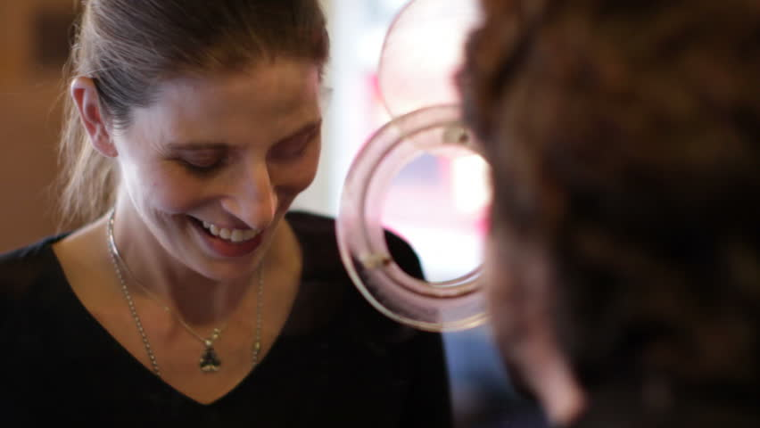 Young woman buys a ticket at a theater box office. Close up view from inside the