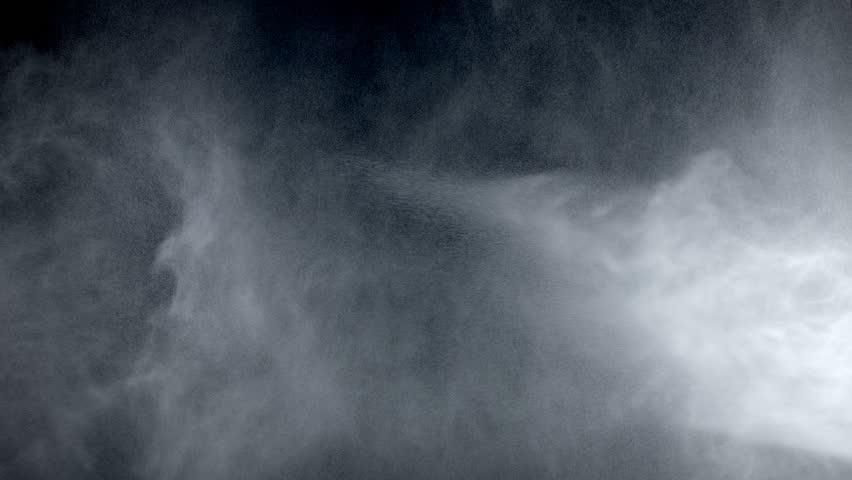 Water fog like drops spread in the air against blackscreen.