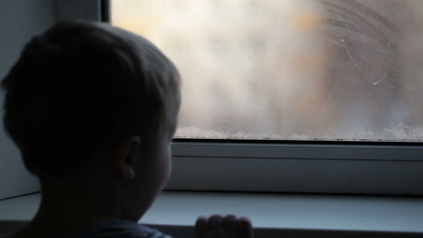 stock video of little boy watching through the misted