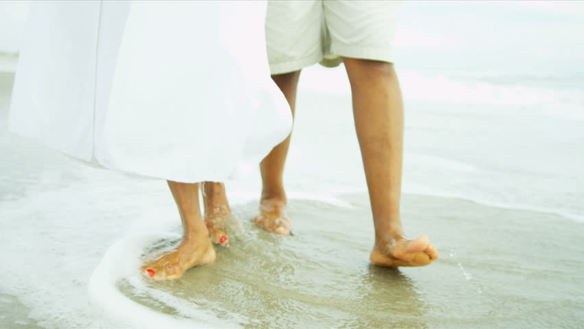 lower body legs of mature african american couple walking on wet