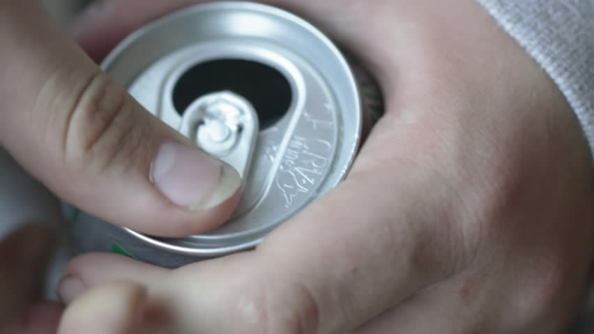 Teenage hands open a can of soda. Shot with a macro lens and shallow depth of
