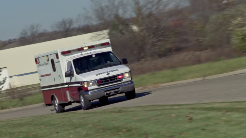Ambulance driving on empty country road with lights flashing in daytime. Canted