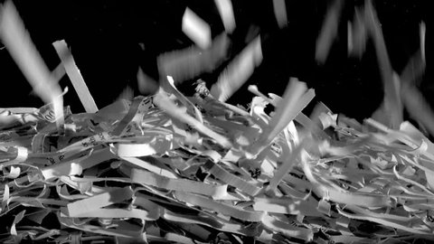 Papers scraps falling from a shredder gradually fill up the screen.