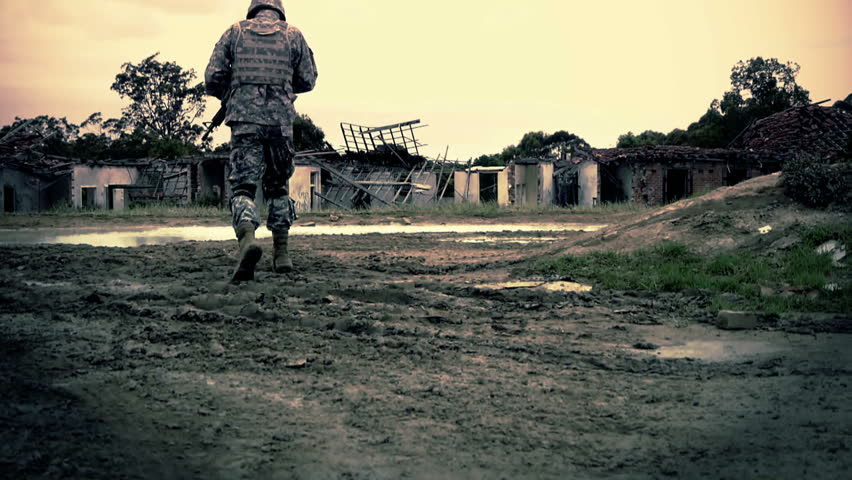 Graded shot of army soldier walking through ruins