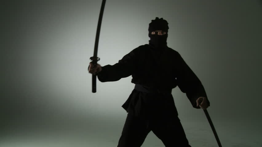 Masked ninja assassin unsheathes a sword and turns to face the viewer.