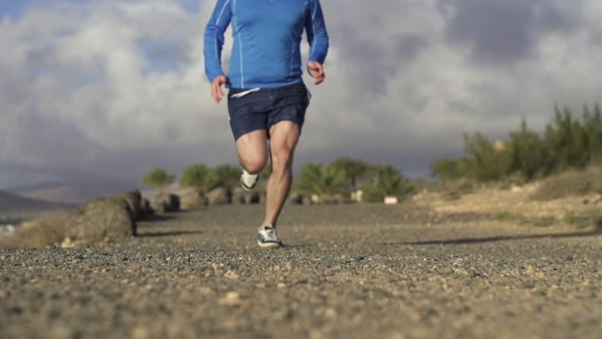 Man jogging in on dirt track, super slow motion, shot at 240fps