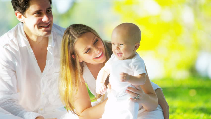 Close up smiling Caucasian parents sitting on grass in park holding up their cute young baby son shot on RED EPIC | Shutterstock HD Video #3763286