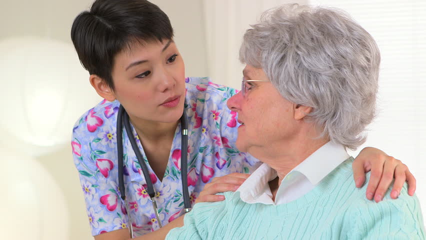 Chinese nurse talking to Caucasian patient