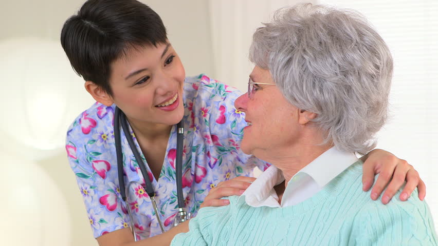 Asian nurse talking to Caucasian patient