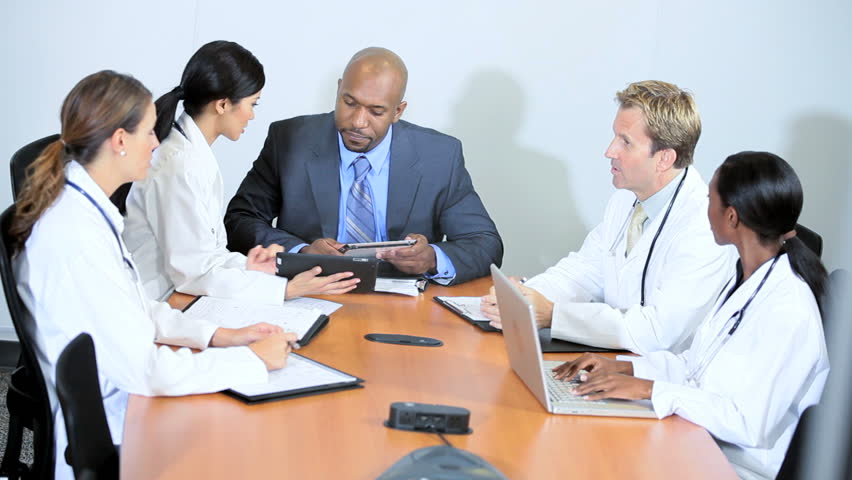 African American financial advisor meeting team medical executives to discuss hospital budgets