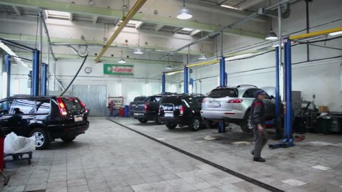 Man walks in car service center with many cars, panoramic motion