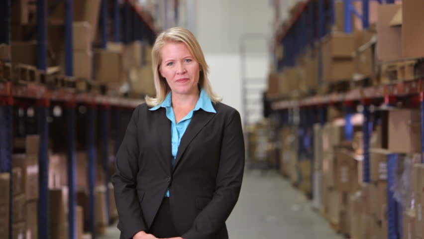 Female manager stands between shelves looking at camera before smiling and crossing arms. Shot on Canon 5d Mk2 with a frame rate of 30fps