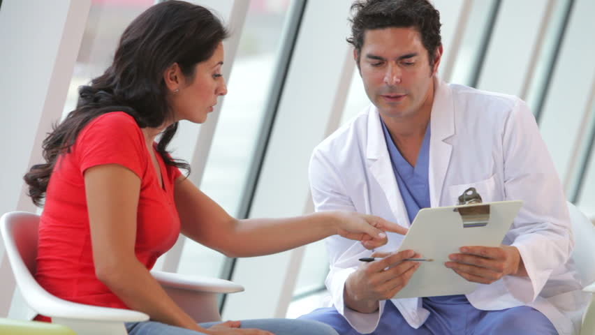 Doctor discusses female patients notes on clipboard. Shot on Canon 5d Mk2 with a frame rate of 30fps #3781346