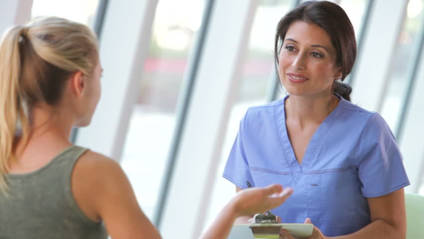 Female nurse taking notes from teenage patient sitting in chair. Shot on Canon 5d Mk2 with a frame rate of 30fps