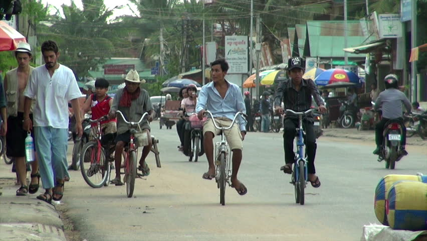 SIEM REAP, CAMBODIA - CIRCA JUNE 2011: A main street footage where local people and tourists walk down or pass through the street by car, bicycle, tuk-tuk and motorbike.