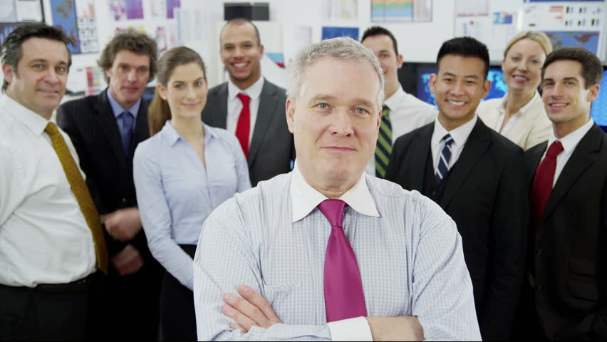 Portrait of a mature businessman who is standing in front of the rest of his diverse and multi ethnic business team. They all look into the camera and smile.  | Shutterstock HD Video #3786053
