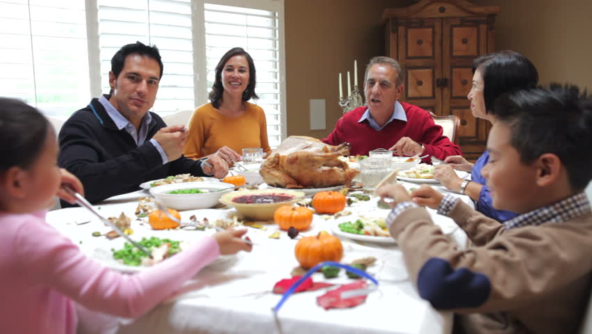 Camera Tracks Across Table As Extended Family Sit And Enjoy Thanksgiving Dinner Shot On Canon