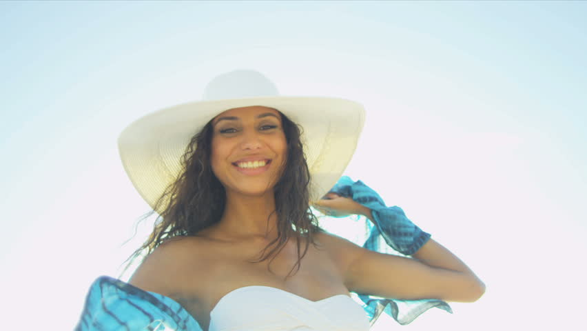 Young Hispanic beach girl wearing white swimsuit straw hat having fun smiling to camera on beach sun lens flare close up shot on RED EPIC