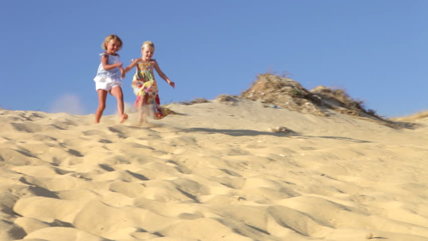 Two young girls running down sand dune past camera position. Shot on Canon 5d Mk2 with a frame rate of 30fps