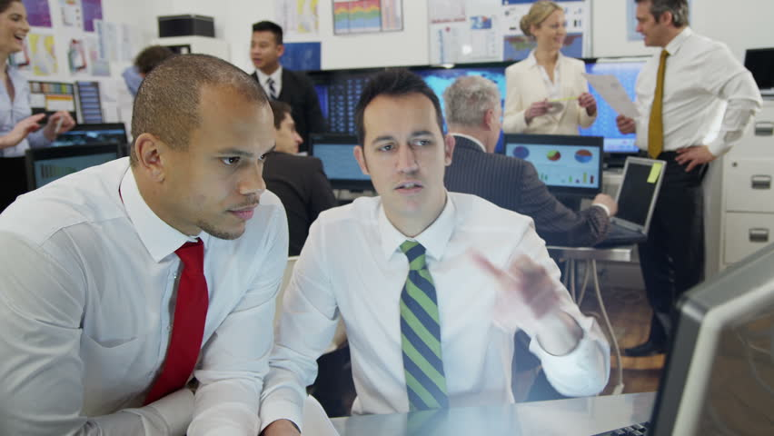 Two young male financial traders are working in a busy office filled with computers. They are discussing stock market prices and profits, as the rest of their team are hard at work in the background