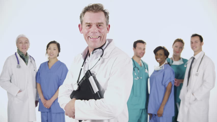 Portrait of a team of medical personnel of mixed ages and ethnicity isolated on white. They are talking amongst themselves then they all look to the camera and smile. In slow motion. | Shutterstock HD Video #3823178