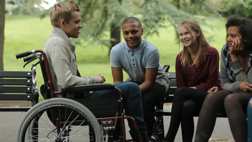 Teenager in wheelchair hangs out with his friends