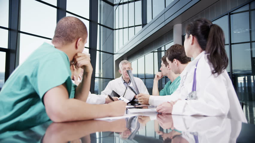 A diverse team of medical personnel are having a meeting in a light, modern private health care facility. They are discussing a patient's x-ray results and looking for a diagnosis. #3848756